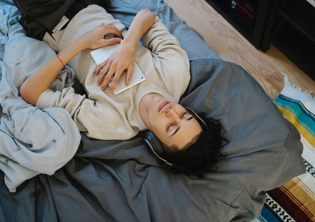 Young male lying down on a bed, relaxing while listening to 8D audio on his headphones