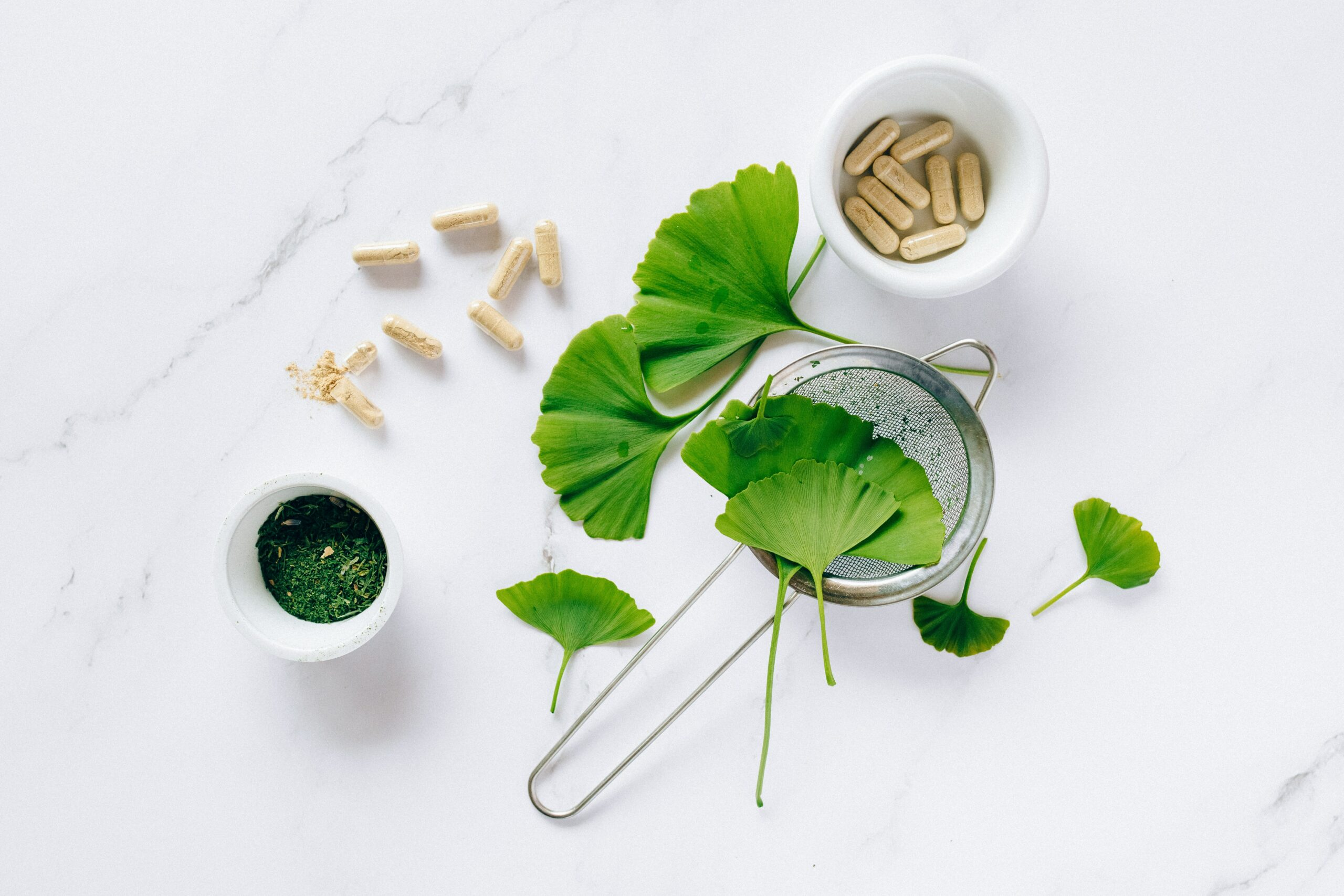 gingko biloba leaves capsules powder and tea arranged on a tabletop
