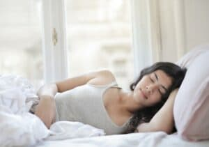 Young woman going through stages of sleep in her bed