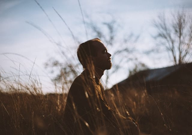 Man meditating in a field to decrease anxiety