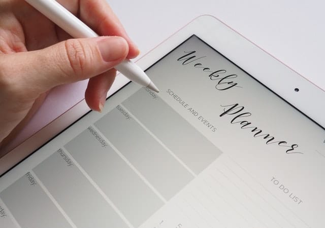Woman using white tablet planner, to restructure time from schedule