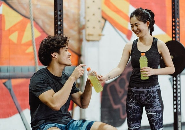 Man and woman smiling drinking pre workout, containing agmatine sulfate