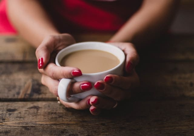 Woman's hands holding a white cup of coffee
