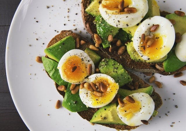 Avacado, eggs, and nuts, sources of L-Tyrosine, on a white plate