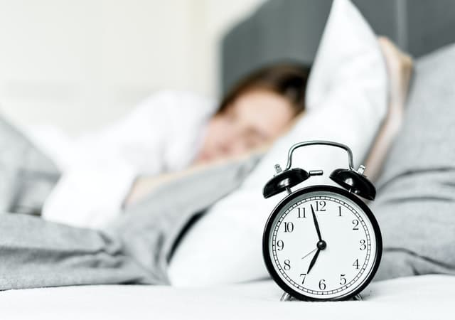 Alarm clock, a great way to balance cortisol rhythm, on a night stand next to woman sleeping in bed